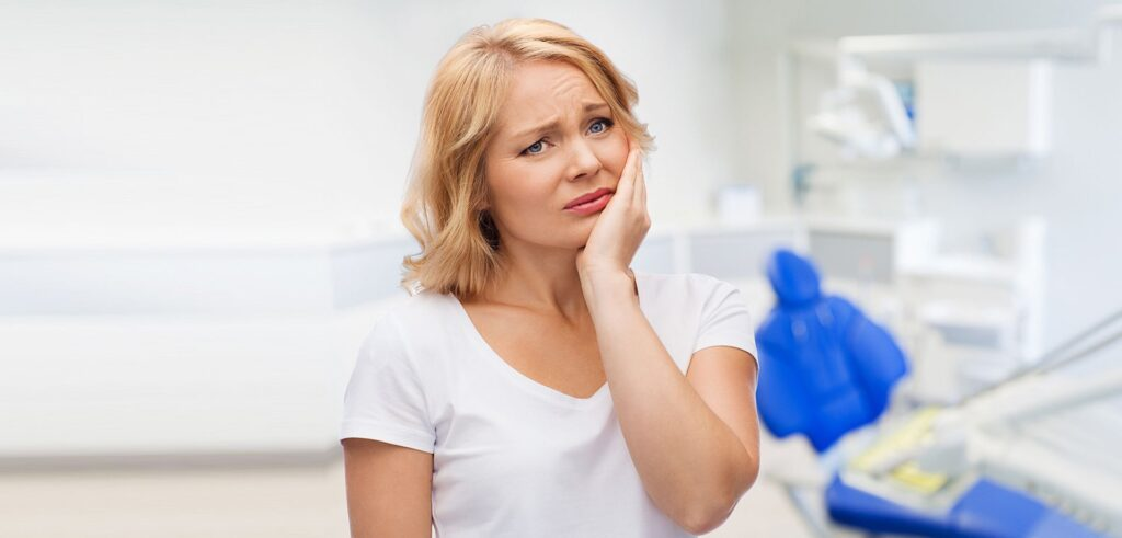 Woman with tooth pain undergoing dental check up