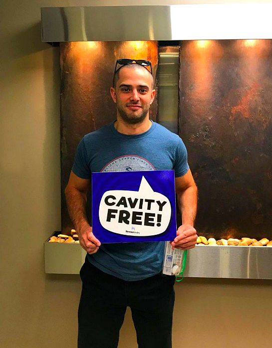 Satisfied male client of RenovaSmiles holding cavity-free signage