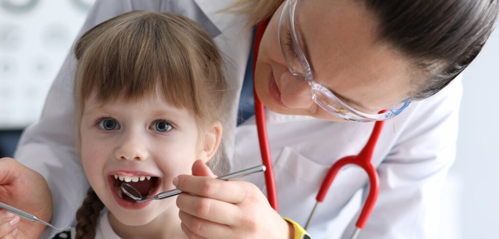 Dentist checking a young girl's teeth and gums